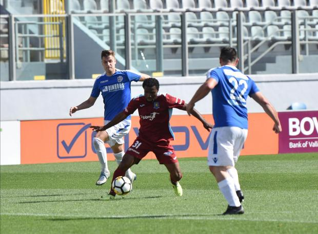 Gżira's Ndubisi Okoye tries to find an opening in the Mosta defence. Photo: Mark Zammit Cordina