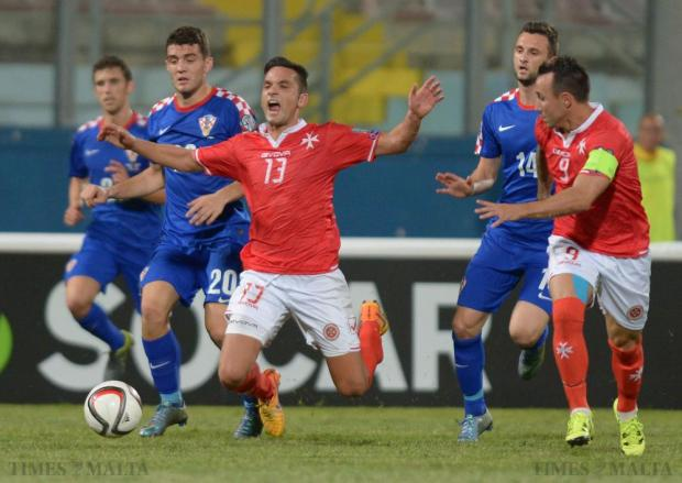 Malta's Andre Schembri (centre) is brought down by Croatia's Mateo Kovacic (left blue 20) during their UEFA European Championship Qualifying match at the National Stadium in Ta'Qali on October 13. Photo: Matthew Mirabelli