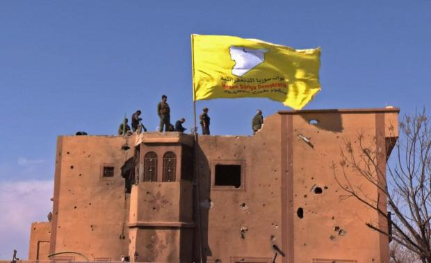 US-backed Syrian Democratic Forces (SDF) raise their flag atop a building in the Islamic State group's last bastion in the eastern Syrian village of Baghuz. Photo: AFP
