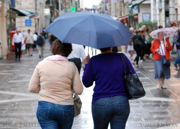 Two women share an umbrella as they walk up Republic Street in Valletta on October 28. Photo: Mark Zammit Cordina