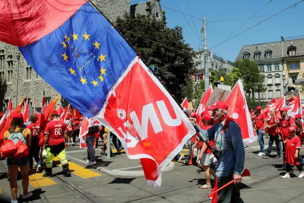 A Swiss construction worker carries flags of Swiss workers union Unia and another of the European Union during a demonstration in Zurich.