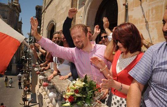 Joseph Muscat and his wife Michelle wave to Labour supporters with Anglu Farrugia, deputy leader for Parliamentary affairs, behind them.