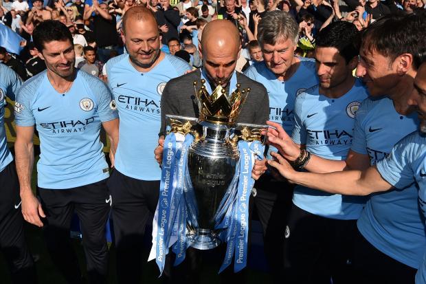 Manchester City's Spanish manager Pep Guardiola (centre) kisses the Premier League trophy.