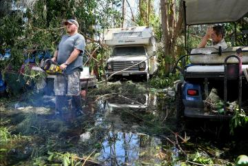 Carl Nicholson prepares to remove debris and fallen trees from his flooded yard following Hurricane Irma near Jerome, Florida. Photo: Reuters