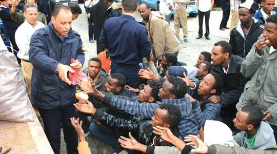 A Libyan policeman distributing bread to migrants who were rescued yesterday off a boat that sank in a violent storm off the coast of Libya on Sunday.