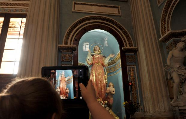 A tourist takes a photo of a statue in the Mosta Parish church on October 11. Photo: Chris Sant Fournier