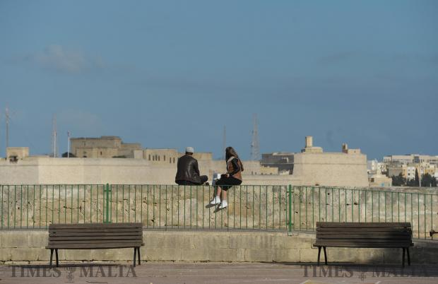 A couple sit on the bastions in Floriana on February 19. Photo: Matthew Mirabelli