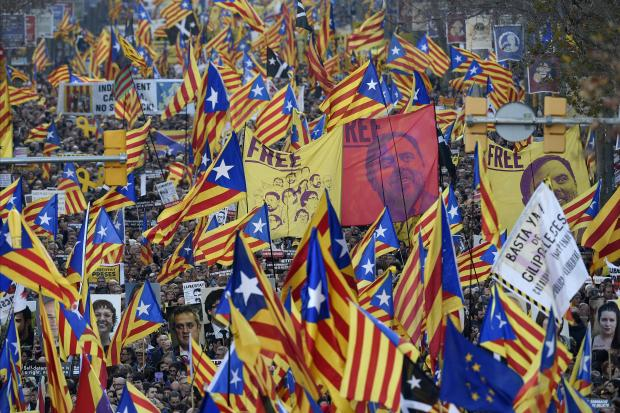 Demonstrators hold portraits of jailed Catalan separatists and wave Catalan pro-independence Estelada flags during a protest.