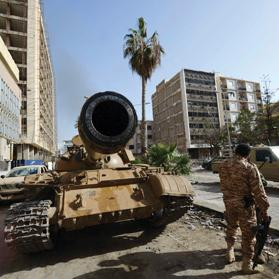 A soldier of the Libyan pro-government forces stands near a tank outside the central bank, near Benghazi port, yesterday. Photos: Reuters