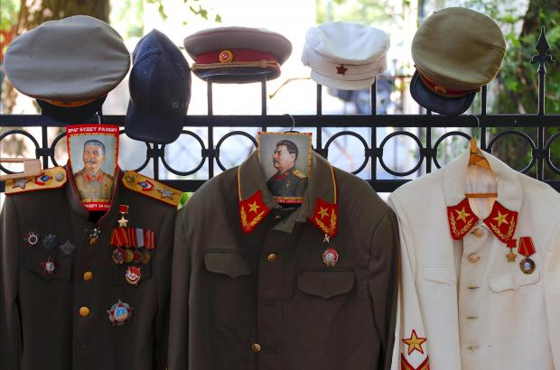 Russian military costumes for tourists to wear hang from a fence outside the entrance to Stalin's Bunker.