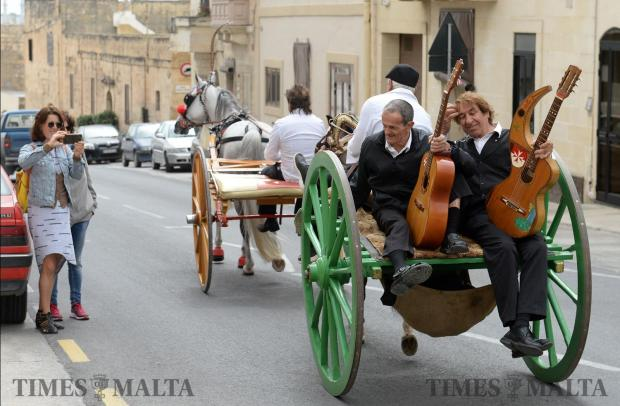 A tourist takes a photo of a horse drawn cart making its way to Marsaxlokk for the feast of San Girgor on April 4. Photo: Matthew Mirabelli