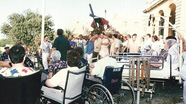 June 7, 1999: Sick and old people pray to Jesus the Redeemer as his effigy passes by St Vincent de Paul Residence, Luqa.