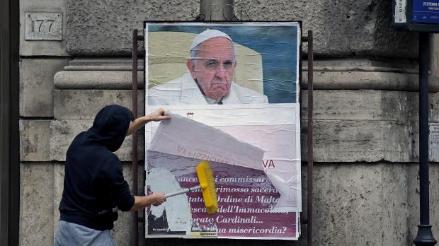 "A worker covers with a banner reading ""illegal poster"" a poster depicting Pope Francis and accusing him of attacking conservative Catholics."
