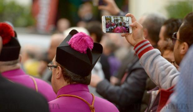 Tourists take photos of the coffin of Archbishop Emeritus Joseph Mercieca as it is carried to St John's Co-Cathedral in Valletta on March 21. Photo: Matthew Mirabelli