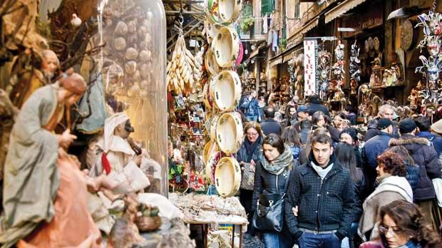 People walk in Via San Gregorio Armeno in Naples which hosts many artisans who make world renowed hand-crafted Nativity scenes. Artisans warn they may not be around for much longer as the economic crisis hits their family businesses. Photo: Carlo Hermann/AFP