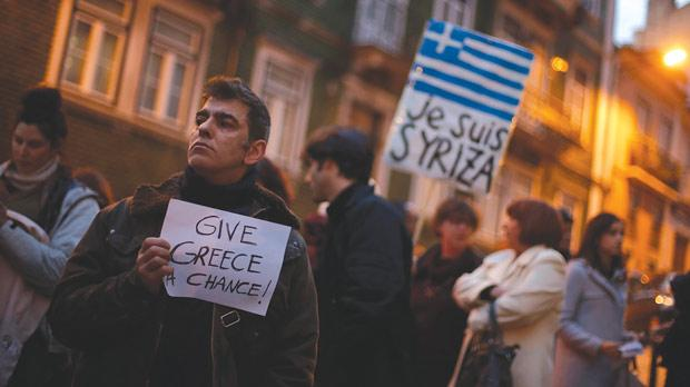A man holds a placard during a vigil to support the newly-elected Greek government, outside the European Commission headquarters in Lisbon. Photo: Rafael Marchante/Reuters