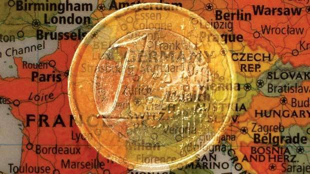A €1 coin and a map of Europe. Photo: Kai Pfaffenbach/Reuters