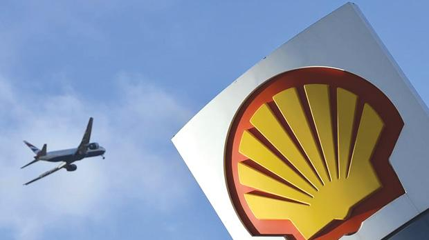 A passenger plane flying over a Shell logo at a petrol station in west London. Photo: Toby Melville/Reuters