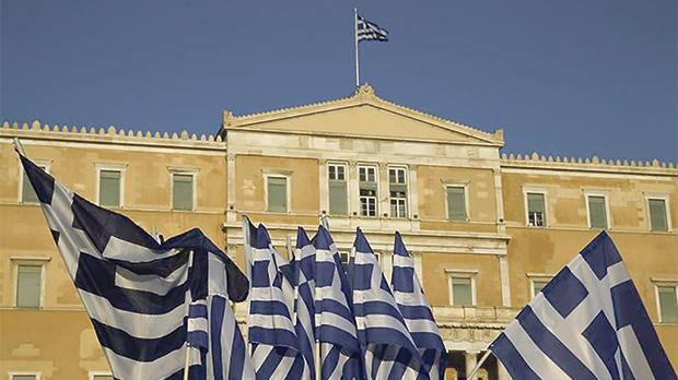 The Greek Parliament seen behind flags displayed for sale in Athens, Greece. Photo: Yannis Behrakis/Reuters