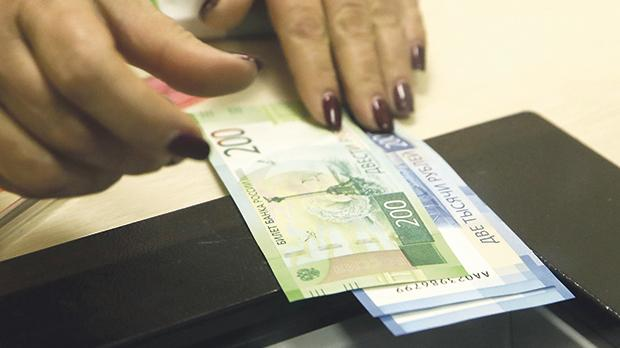 A cashier holds rouble banknotes in a Moscow bank in Russia. Photo: Reuters