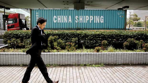 A man passing by a shipping container loaded onto a truck nearby a port in Tokyo, yesterday, as Japan's economy shrank 0.9 per cent in the three months to September. Photo: Reuters