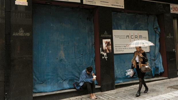 A beggar sits in front of a closed shop at a central pedestrian street of Athens yesterday as international lenders failed for the second week to reach a deal to release emergency aid for Greece and will try again next Monday. Photo: Reuters