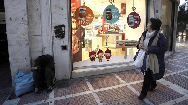 A man begs outside a shop in Athens as southern Europe experiences a bleak Christmas as the area worst hit by the eurozone debt crisis. Continued recessions are expected in Greece, Portugal, Italy and Spain next year. Photo: Reuters