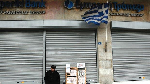A lottery ticket vendor sitting outside an Emporiki Bank branch in Athens. Photo: Reuters