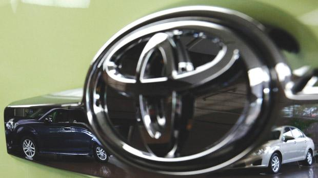 Toyota's Corolla Fielder (left) and Corolla Axio are reflected in a Toyota Forte's logo at the company's headquarters in Tokyo. Photo: Reuters