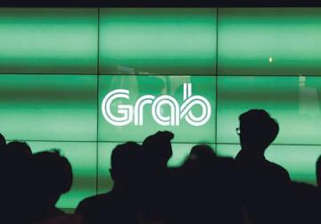 People wait for the start of ride-hailing company Grab's fifth anniversary news conference in Singapore. Photo: Reuters