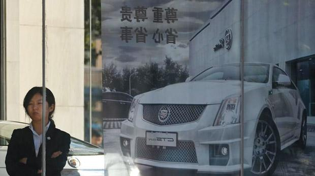 A woman standing next to a Cadillac CTS car poster outside a dealership in Beijing. Photo: Petar Kujundzic/Reuters