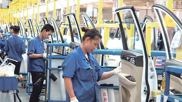 Employees at a production line inside a factory of Saic GM Wuling, in Guangxi Zhuang Autonomous Region, China. Photo: Norihiko Shirouzu/Reuters