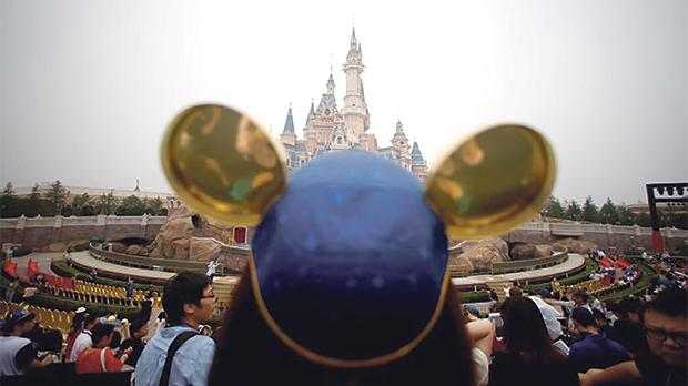 A woman wearing Mickey Mouse ears watches the opening ceremony at Shanghai Disney Resort in Shanghai, China. Photo: Reuters