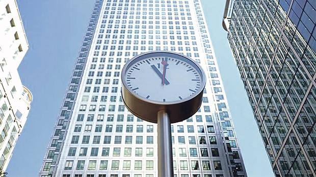 A clock is seen in London's financial centre at Canary Wharf in London, Britain. Photo: Reuters