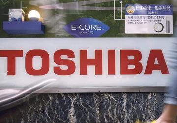 Pedestrians walk past a logo of Toshiba Corp in Tokyo, Japan. Photo: Yuya Shino/Reuters
