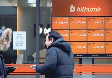 Two men speaking in front of an electric board showing exchange rates of various cryptocurrencies at Bithumb cryptocurrencies exchange in Seoul, South Korea. Photo: Reuters