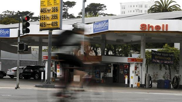 A cyclist riding past a sign showing the prices of gas at a filling station in San Francisco, California. Photo: Robert Galbraith/Reuters