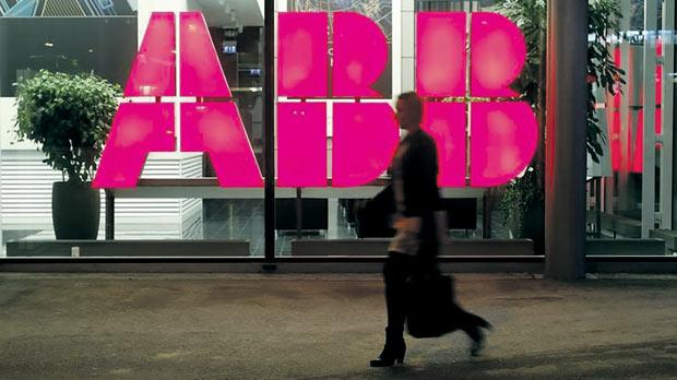 A woman walking past the logo of Swiss industrial group ABB at an office building in Zurich. Photo: Arnd Wiegmann/Reuters