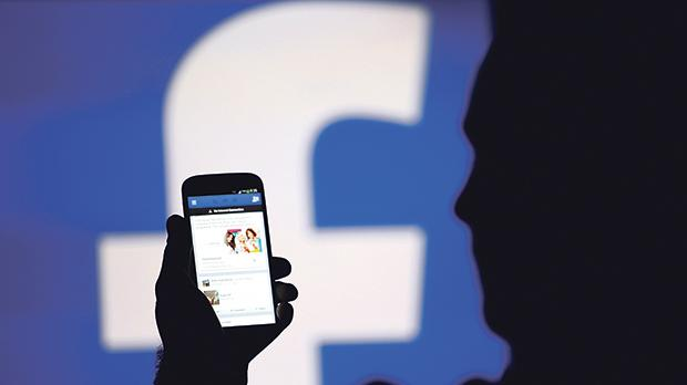 A man is silhouetted against a video screen with a Facebook logo. Photo: Dado Ruvic/Reuters