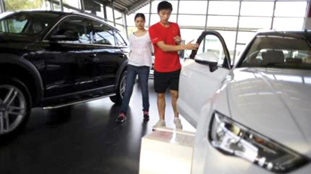 People looking at a car inside an Audi dealership in Shanghai, China. Photo: Carlos Barria/Reuters