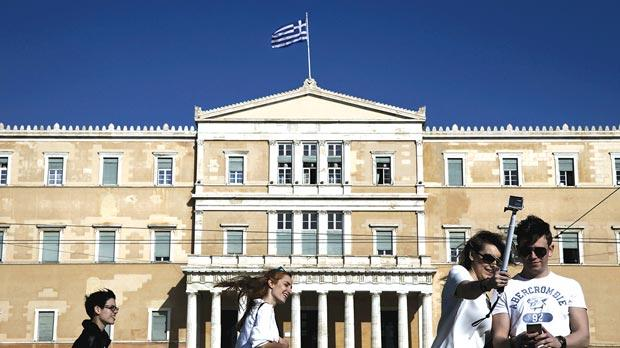 People walking past the Parliament building in central Athens. Photo: Reuters
