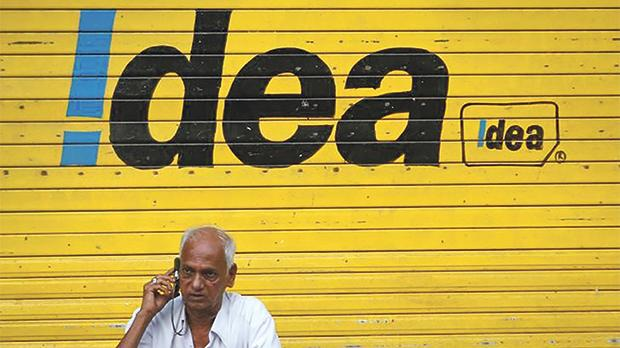 A man speaking on his mobile phone in front of a shop displaying the Idea Cellular Ltd's logo in Mumbai, India. Photo: Danish Siddiqui/Reuters