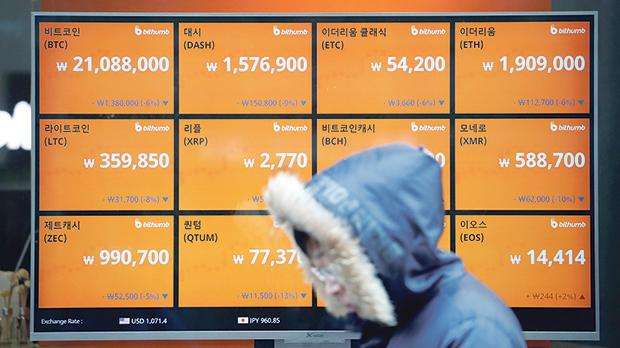A man walks past an electric board showing exchange rates of various cryptocurrencies in Seoul, South Korea. Photo: Reuters