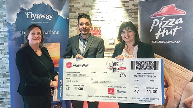 Matthew Fenech being presented with the package by Flyaway director Josianne Tonna and Pizza Hut franchise manager Nathalie Xuereb Saydon.