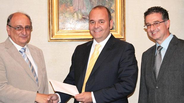 Economy, Investment and Small Business Minister Chris Cardona presenting a Patronage Refund to Green Pak Coop Society member Louis Cardona, managing director of International Merchants, in the presence of Mario Schembri.
