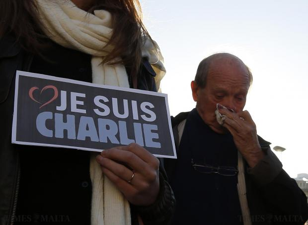 "A man wipes away tears near a woman holding a placard that reads, ""I am Charlie"" during a silent protest and tribute to the victims of the shootings by gunmen at the offices of the satirical weekly newspaper Charlie Hebdo in Paris, in Valletta January 11. Photo: Darrin Zammit Lupi"