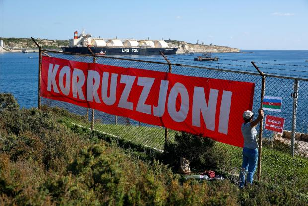Activists hanging a banner at Delimara shortly after the story broke. Photo: Reuters