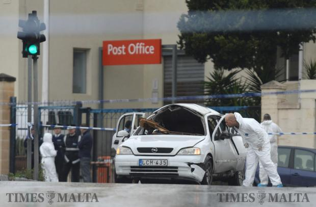 A police officer looks into the car which exploded after a car bomb went off killing 65 Victor Calleja, of Ħamrun. The incident happened in Qormi just outside Maltapost offices on January 29. Photo: Matthew Mirabelli