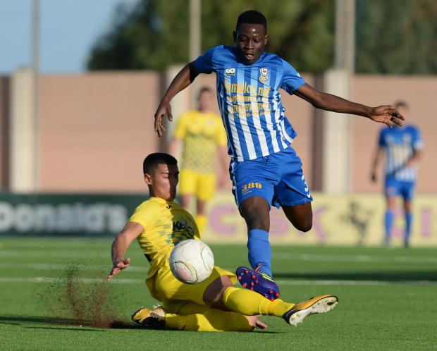 Pieta's Godwin Mensah, (right) charges forward with the ball during their Division 1 match against San Gwann at the Centenary Stadium in Ta'Qali on November 19. Photo: Matthew Mirabelli