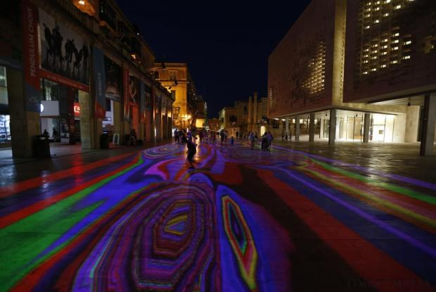Pedestrians walk through Pixels Wave 2015, a giant carpet of moving lights on the ground in an interactive virtual reality installation by Mexican-born experimental and multidisciplinary artist Miguel Chevalier, during the Malta International Arts Festival, at the entrance to Valletta on July 13. Photo: Darrin Zammit Lupi